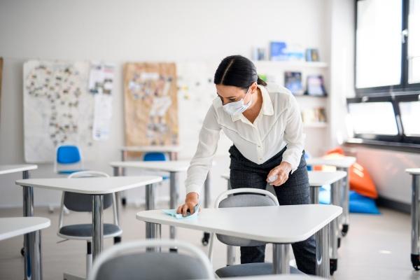 a woman cleaning a school desk
